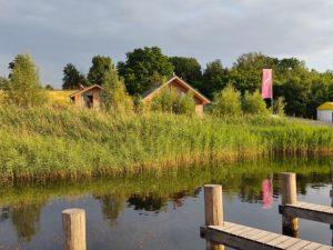 Bootssteg mit Blick auf die Ferienhäuser am See