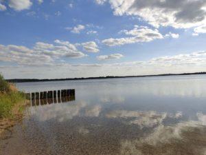 Strand mit Pfosten & spiegelglattes Wasser
